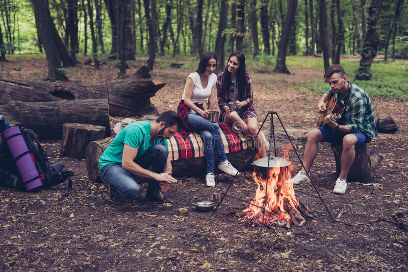 Fire place, four cheerful serene tourists are sitting around. Chilling, blond guy plays the guitar, other opens can of conserve, girls drink tea, nice eve at stock photography
