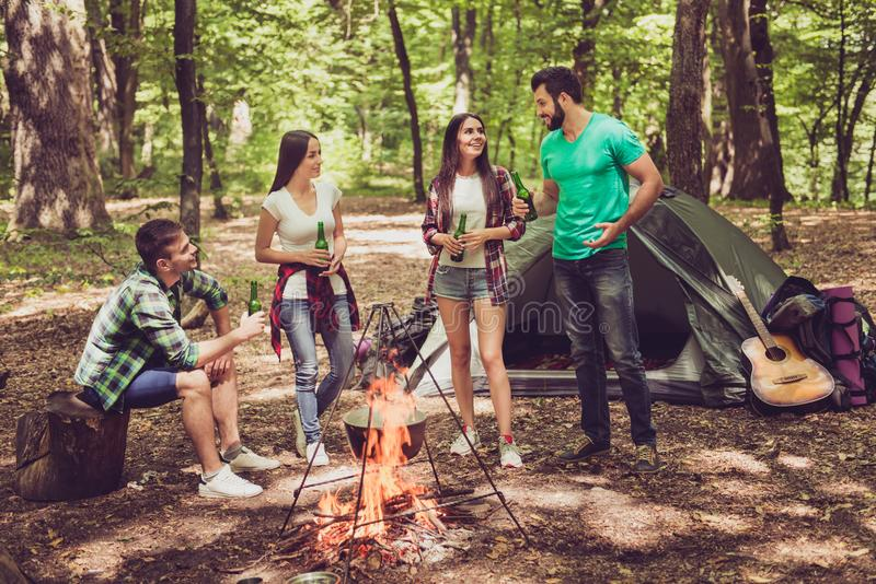 Fire place, four cheerful tourists friends are around, chilling, having beer, nice sunny summer day, campsite royalty free stock photos