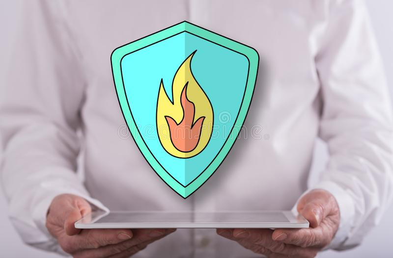Concept of fire protection. Fire protection concept above a tablet held by a man in background stock images