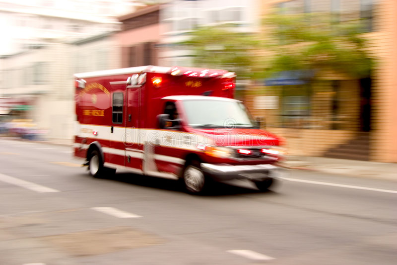 Fire Rescue. A fire rescue vehicle blazes by, it's sirens whaling. An intensional zoom blur gives a feeling of a rushed tension to the scene royalty free stock photos