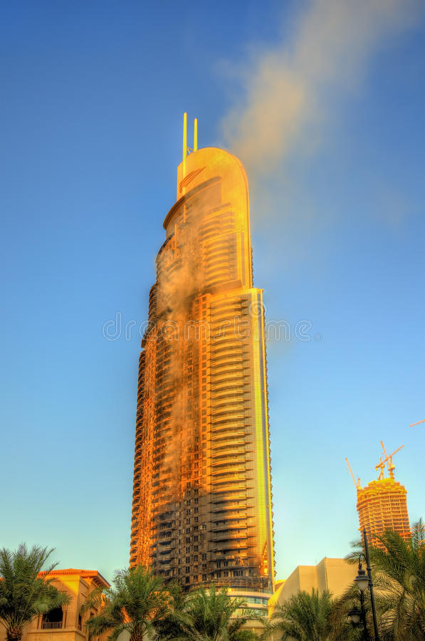 Fire and rescue services near burning Address Downtown Hotel. DUBAI, UAE - JANUARY 1: View of the Address Downtown Hotel on fire in Dubai on January 1, 2016. The stock photo