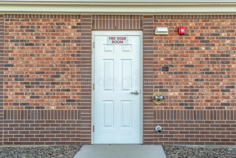 Fire Riser Room sign on the white wood door of a building with red brick wall royalty free stock photos