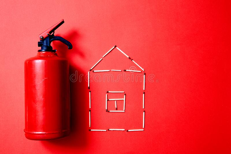 Fire safety, or security and protection concept. Fire extinguisher and the figure of the house of matches. Fire safety or security and protection concept. Fire royalty free stock photo