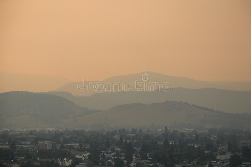 Fire season Kelowna- Sunset with smoky sky- 4 layers of mountains showing stock photos