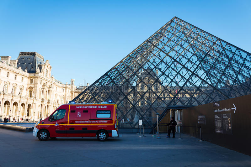 Fire service vehicle at the Louvre pyramid. Paris, France - December 04, 2015: fire service minibus at the pyramid of Louvre museum. The security guard is royalty free stock image