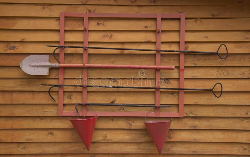 Fire shield with equipment on a wooden wall.  royalty free stock photography