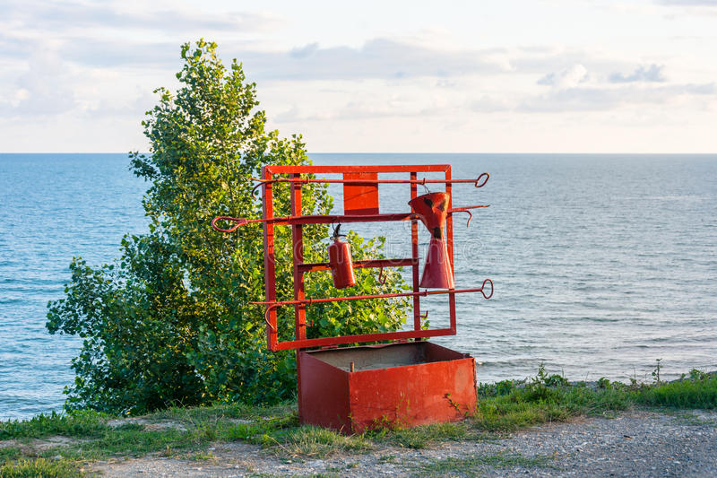 Fire shield by the sea. Bright red fire shield on the shore on a summer day royalty free stock photo