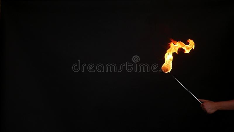 Fire show performance. A man picks gasoline at a torch, slow motion stock photography