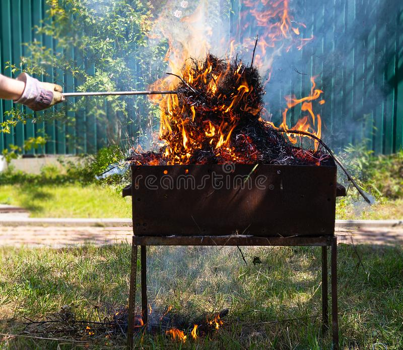 Fire and smoke in the grill, fire, cause of fire, burning BBQ in the yard, burning dry grass stock images
