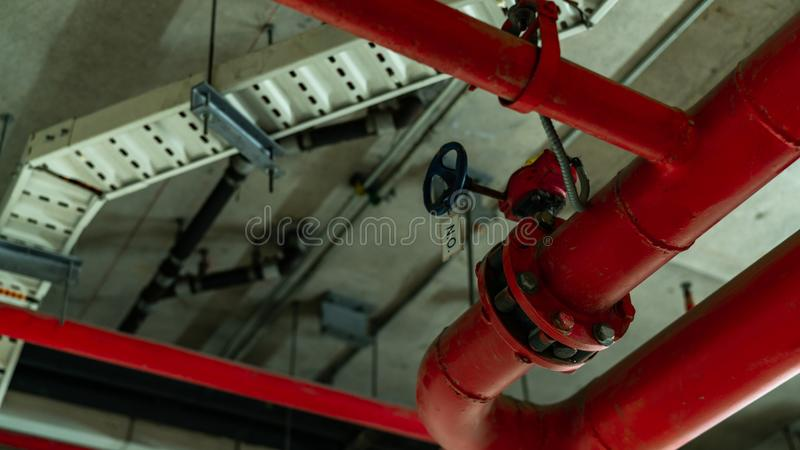 Fire sprinkler system with red pipes hanging from ceiling inside building. Fire Suppression. Fire protection and detector. Main supply water piping in the fire stock photography