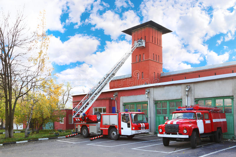 Fire station, two red fire truck. With long ladder, red high tower royalty free stock image