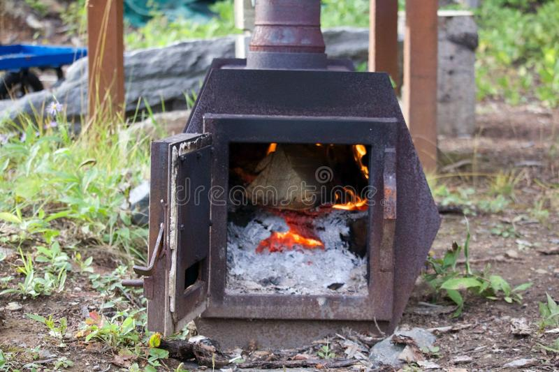 Fire in a Steal Pit. Burning flames in a fire with a smoke stack royalty free stock photography