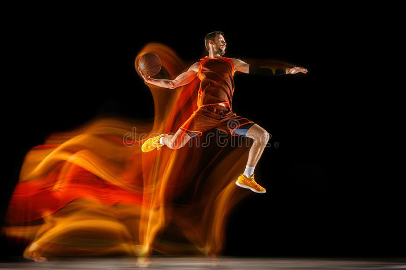 Young caucasian basketball player against dark background in mixed light royalty free stock photo