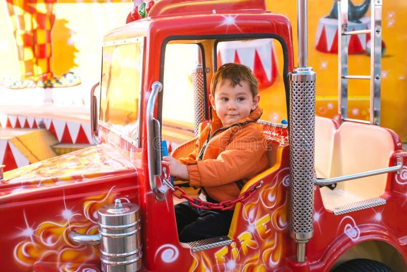 Fire truck ride. Little boy riding a small fire truck in amusement park stock photos