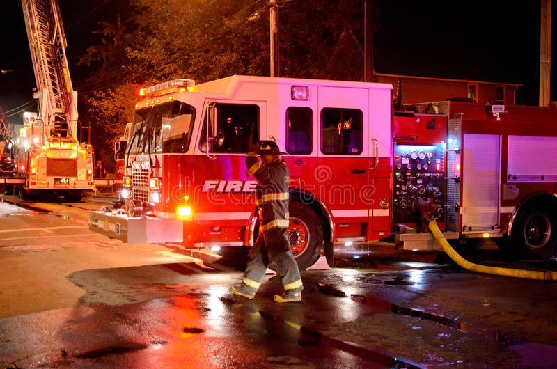 Fire truck at the scene of a fire. Fire truck and safety equipment extinguishing a working fire that ended up being a total loss due to non working smoke alarms royalty free stock photo