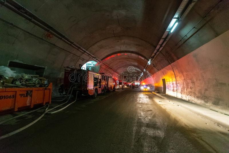 Fire trucks entering a large tunnel with red lights for rescue stock photos