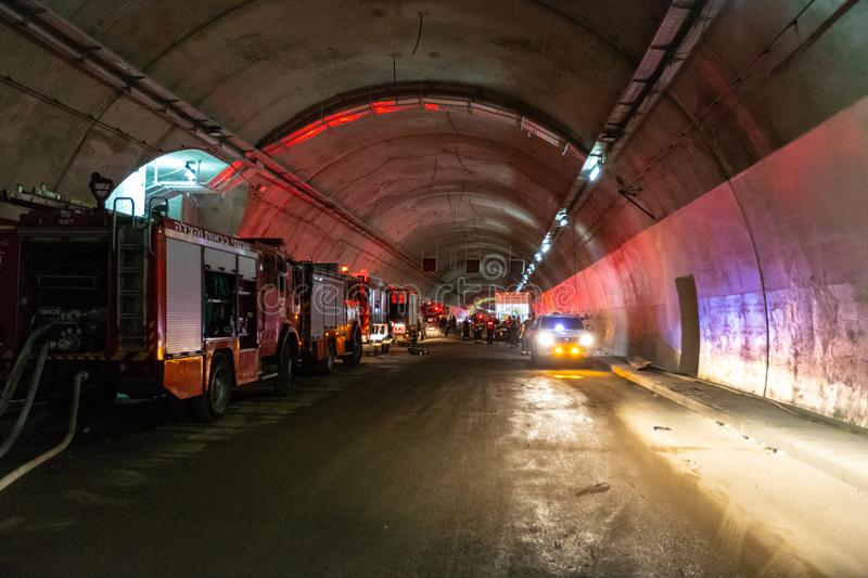 Fire trucks entering a large tunnel with red lights for rescue stock images