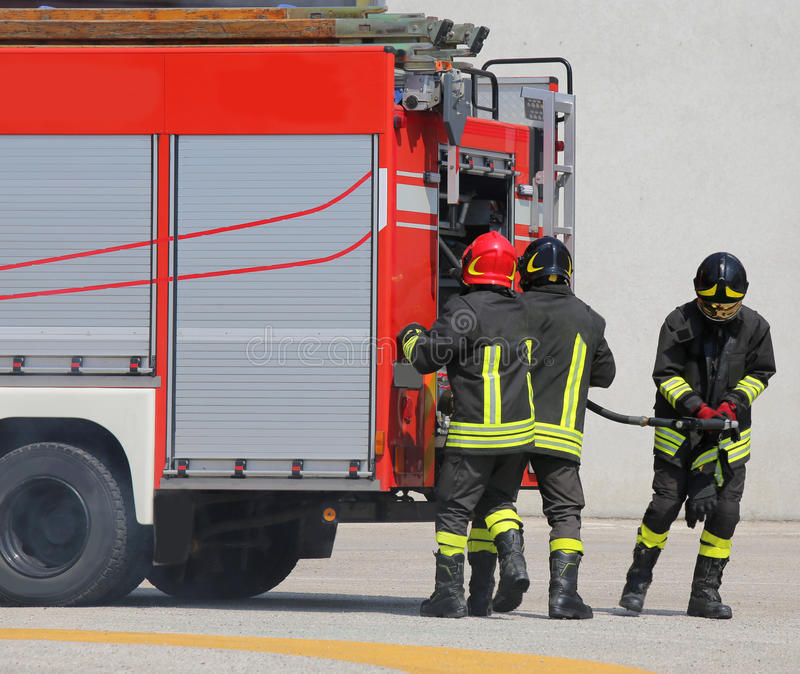 Fire trucks and firefighters with uniforms. And protective helmets stock photography