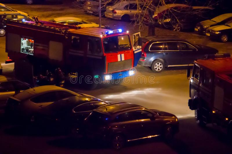 Fire trucks are on the road with flashing lights on at night. A fire brigade in two fire engines arrived at the scene of a strange incident in the dark. Fire royalty free stock images