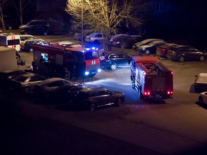 Fire trucks are on the road with flashing lights on at night stock image