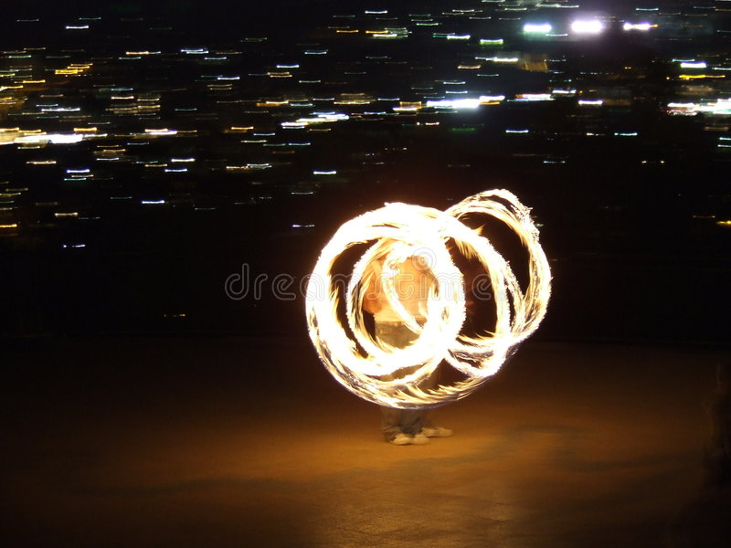 Fire twirling. Blurred fire twirling by night stock photography