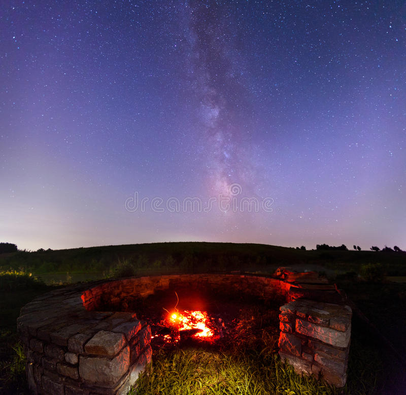 Fire under stars. Fire in the firepit in the countryside with starry skies in the background stock image
