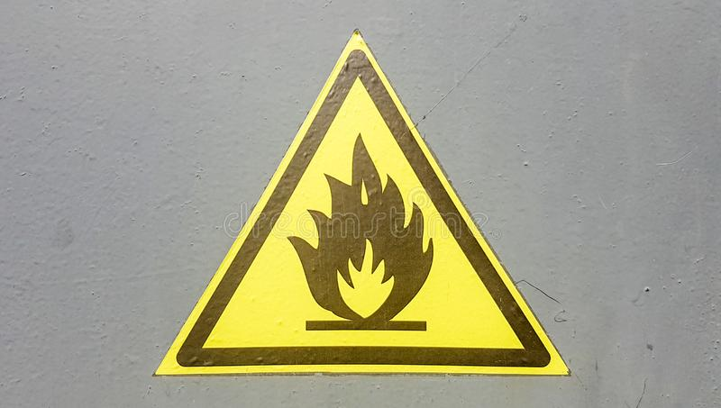 Fire warning icon, sign on a yellow label on a gray background. Flammable. Yellow triangle on a metal wall. Background with copy. Space stock image