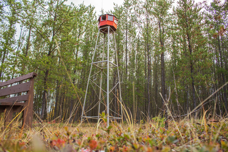 Fire watch tower replica. A red replica of a fire watch tower in front of green trees stock image