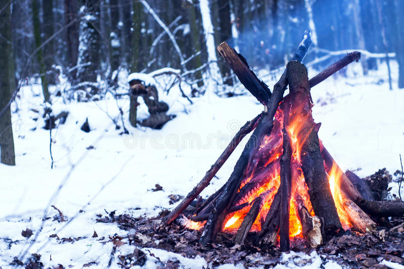 Fire in the winter forest. Couple in love near the fire, winter, snow royalty free stock photos