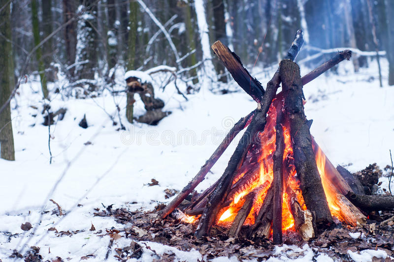 Fire in the winter forest. Couple in love near the fire, winter, snow royalty free stock images