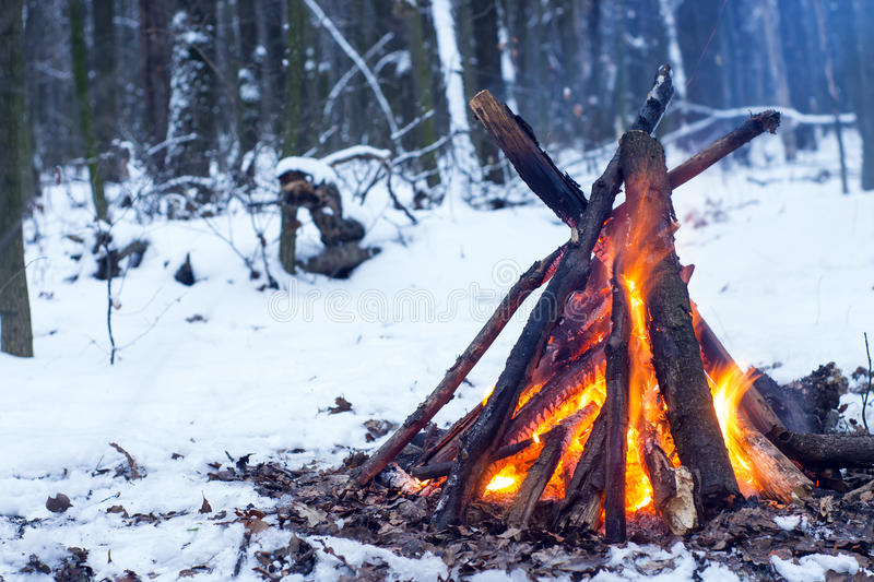 Fire in the winter forest. Couple in love near the fire, winter, snow royalty free stock photography