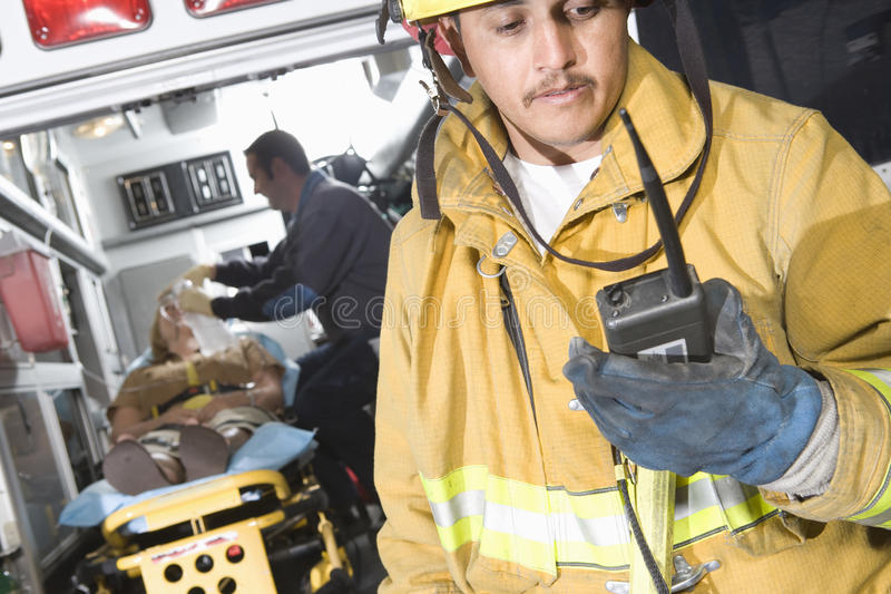 Fire Worker Holding Walkie Talkie With Patient And EMT Doctor In Ambulance. Mature fire worker holding walkie talkie with patient and EMT doctor in the stock photography