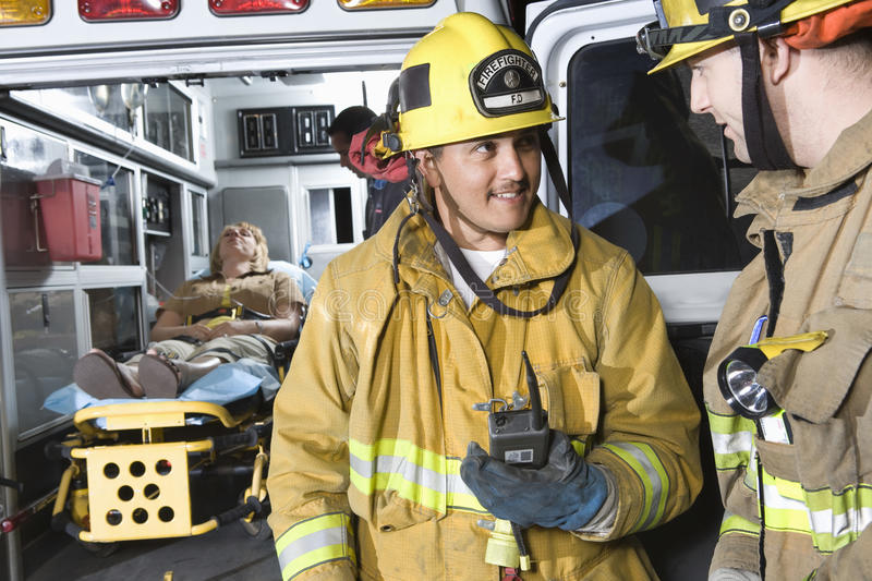 Fire Workers Looking At Each Other. With patient and EMT doctor in the background stock photography