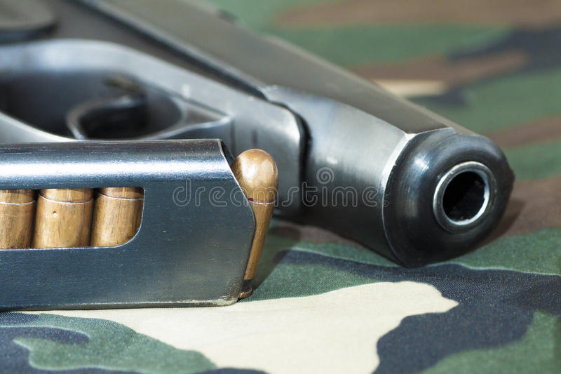 Firearm Pistol And Hand Gun Ammunition on military camouflage background. Firearm Pistol Clip And Hand Gun Ammunition on military camouflage background royalty free stock images