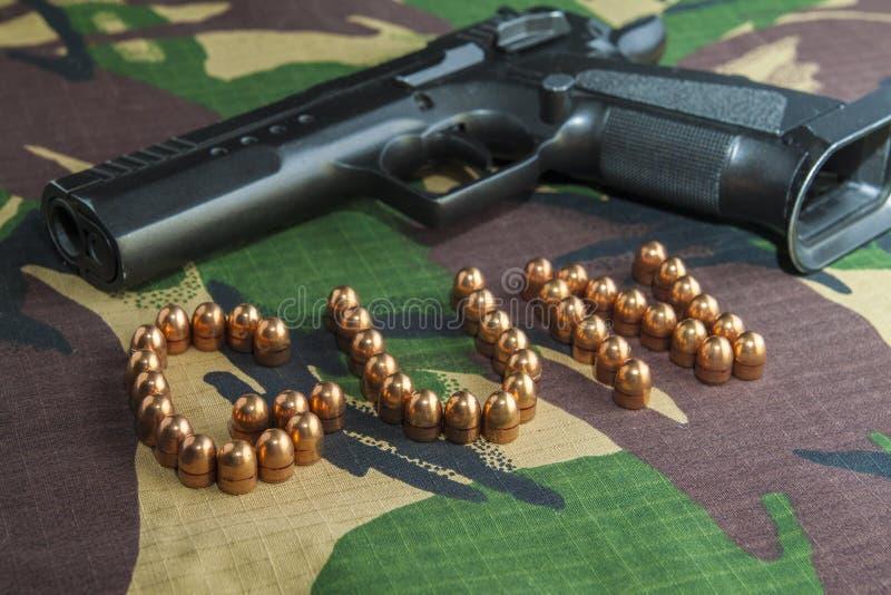 Firearm Pistol on military camouflage background. Firearm Pistol Clip And Hand Gun Ammunition on military camouflage background royalty free stock photography