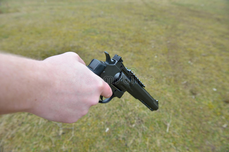 Download Firearms And Security Topic: Hand Man With A Gun Ready To Shoot  Stock Image