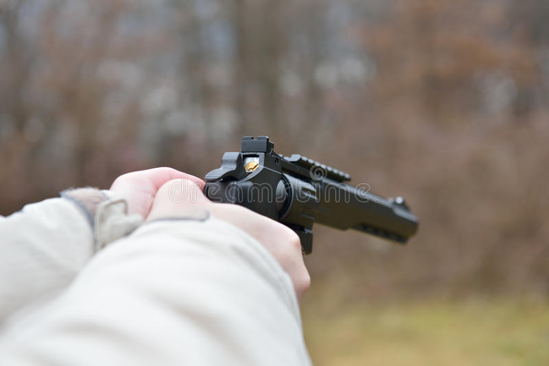 Download Firearms And Security Topic: Hands Man With A Gun Ready To Shoot  Stock Image