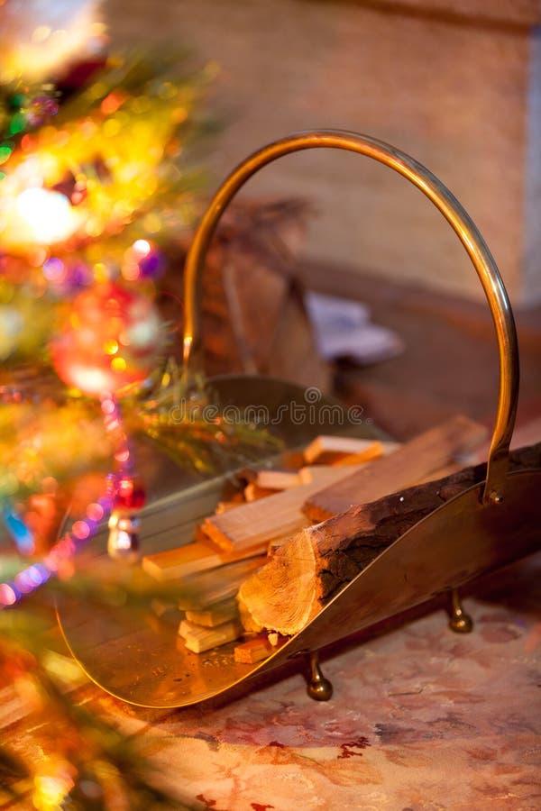 Firebasket de cobre amarillo de la cesta del metal para la leña cerca del árbol de navidad imagen de archivo libre de regalías