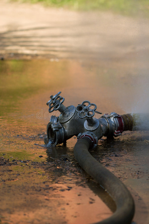 Firecock With Leaking Firehose Stock Photos