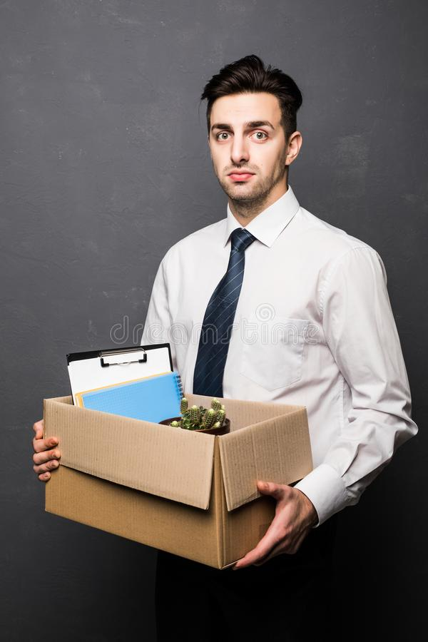 Fired businessman holding box with personal belongings get fired on gray. Fired businessman holding box with personal belongings royalty free stock photos