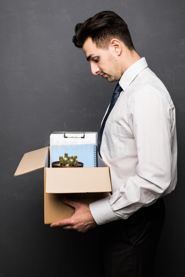 Fired businessman holding box with personal belongings get fired on gray. Fired businessman holding box with personal belongings stock image