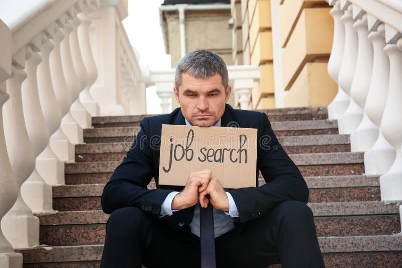 Fired businessman holding piece of cardboard with text JOB SEARCH while sitting on stairs outdoors royalty free stock images