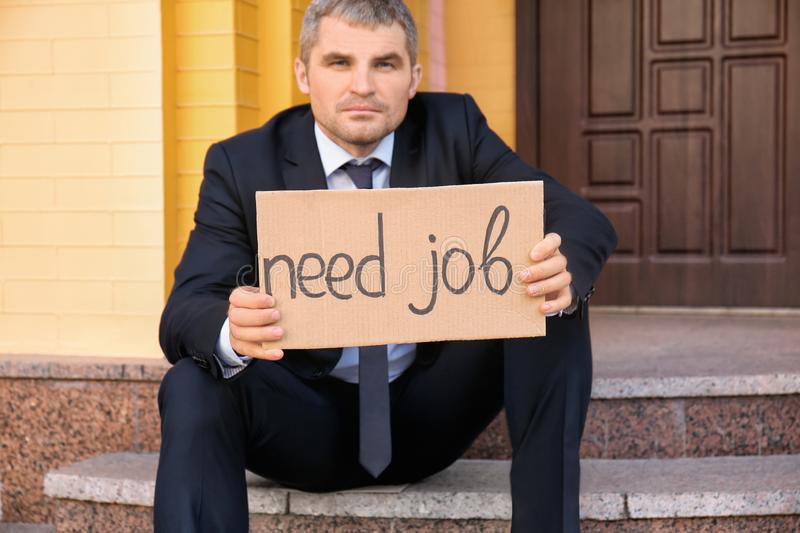 Fired businessman holding piece of cardboard with text NEED JOB while sitting on stairs outdoors stock photos