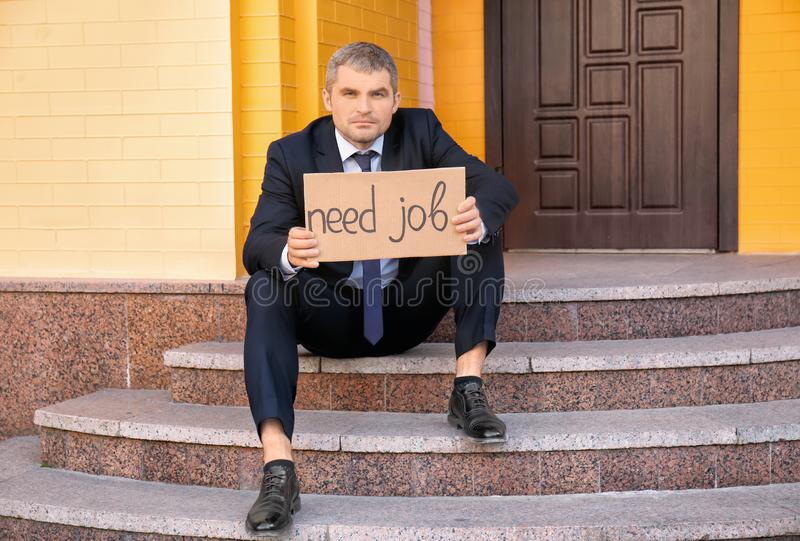 Fired businessman holding piece of cardboard with text NEED JOB while sitting on stairs outdoors stock image