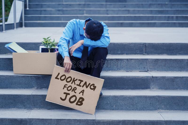 Fired businessman looks sad while sitting on stairs royalty free stock photos