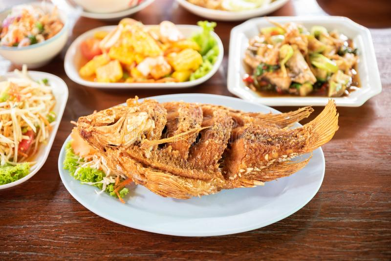 Fired fish with other delicious thai foods on wooden table royalty free stock photography