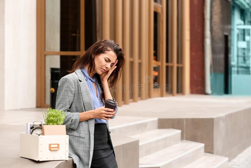 Fired stressed woman with personal stuff and coffee outdoors royalty free stock image