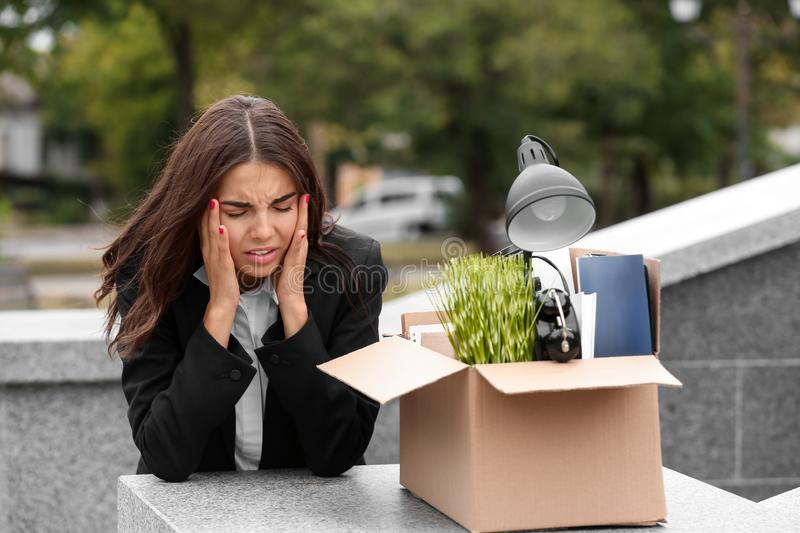Fired stressed worker with personal stuff suffering from headache outdoors stock image