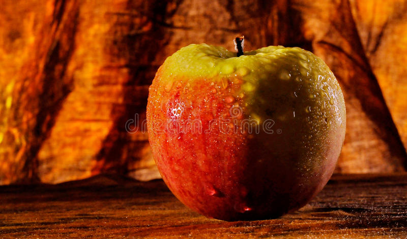 Fired tasty apple. The red apple lies on the table. Still life royalty free stock images