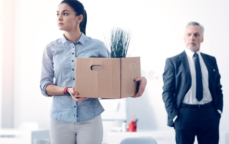 Fired young brunette with box full of stuff leaving office. Dismissal day. Selective focus on an emotionally exhausted female office worker looking into vacancy royalty free stock photo